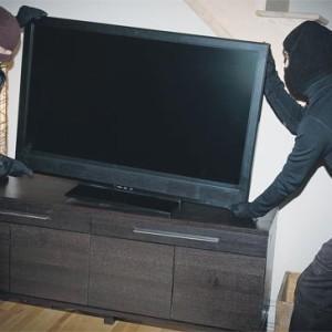 Two burglars stealing flatscreen television