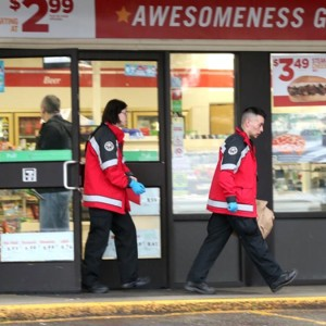 Investigators from the King County Medical Examiner's office work a crime scene at a 7-Eleven convenience store in the Boulevard Park area of South King County early Sunday March 13, 2016. A masked man wielding a hatchet walked into the store swinging, to be fatally shot by a regular customer having his morning coffee.
