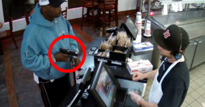 [VIDEO] Armed Robber Tries To Chamber Round During Hold-up, Fails To Feed, Cashier Calmly Hands Over Cash