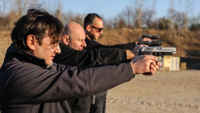 Group of people practice gun shooting on outdoor shooting range