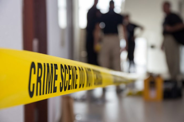 Crime scene tape in building with blurred forensic team backgrou